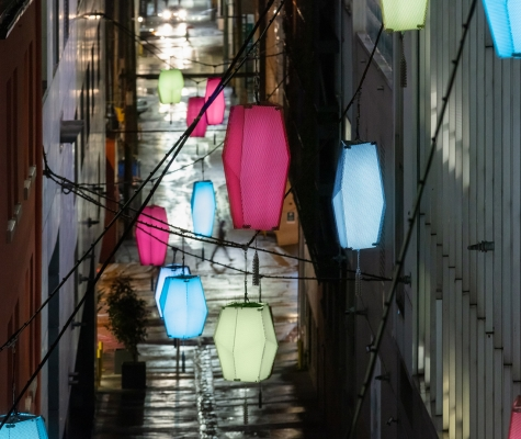 Detail image at dusk of Martin Boyce's art installation, Beyond the Sea, Against the Sun in the TELUS Garden laneway, which consists of a series of suspended lanterns.
